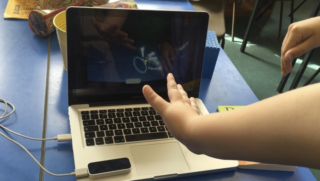 Child's hand waving over a leap motion controller